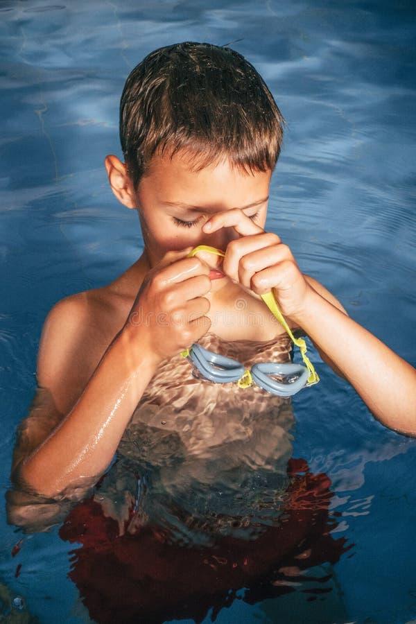 Weinig jongen die aan het zwemmen les in de pool voorbereidingen treffen stock foto's