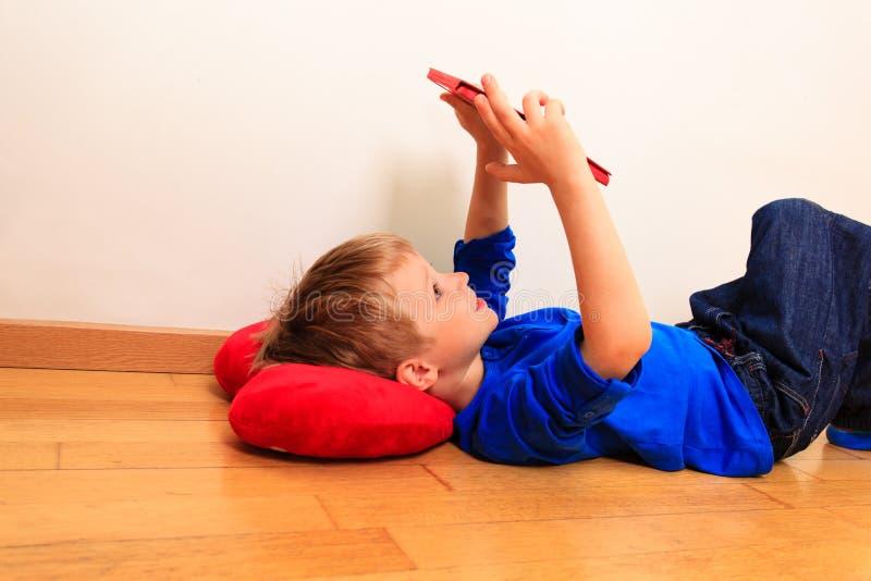 Weinig jongen die aanrakingsstootkussen bekijken, het leren concept stock fotografie