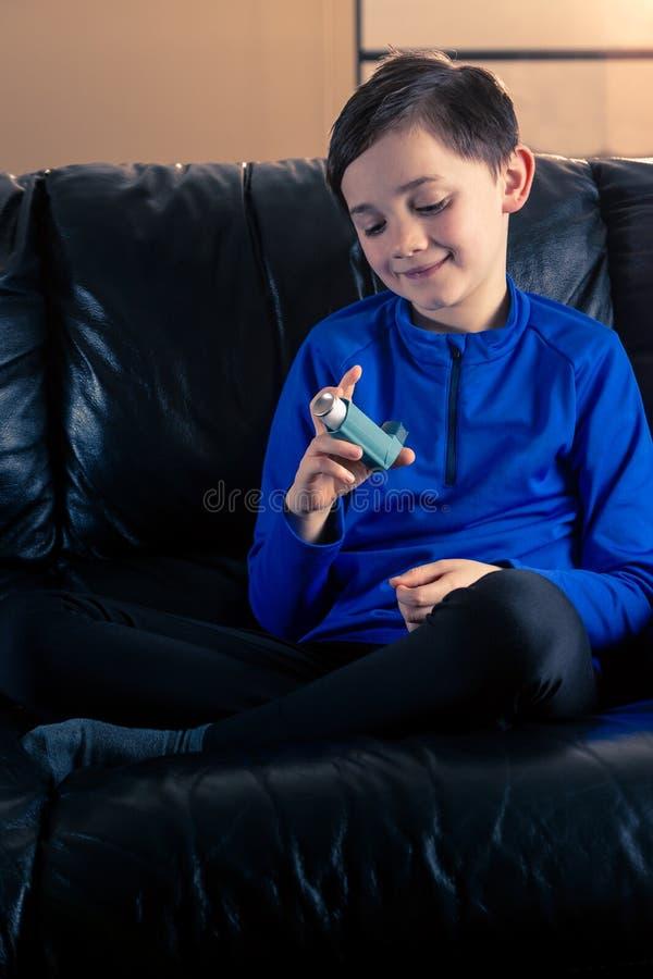 Weinig jongen die astmainhaleertoestel bekijken stock afbeelding