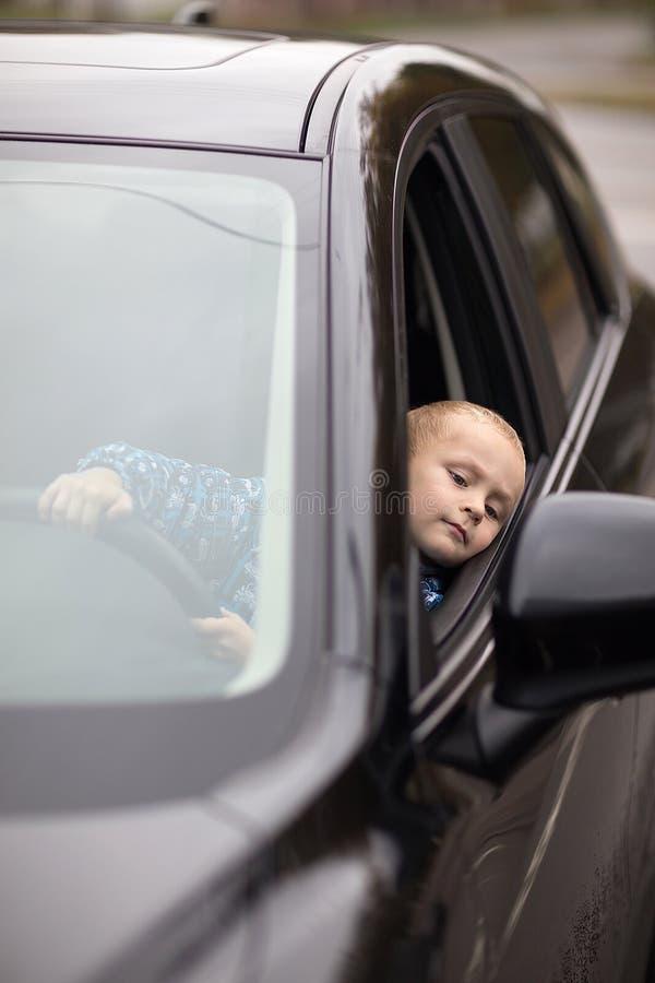 Weinig jongen die auto beweren te drijven stock fotografie
