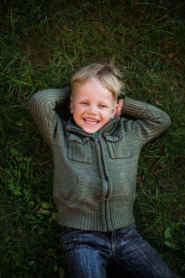 Weinig jongen die bij gras en het lachen liggen stock afbeeldingen