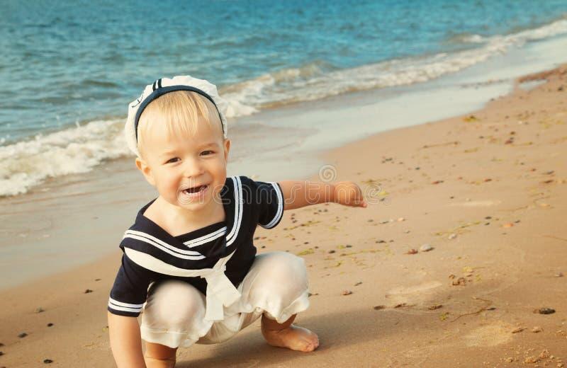 Weinig jongen die bij het strand in strohoed lopen royalty-vrije stock afbeelding
