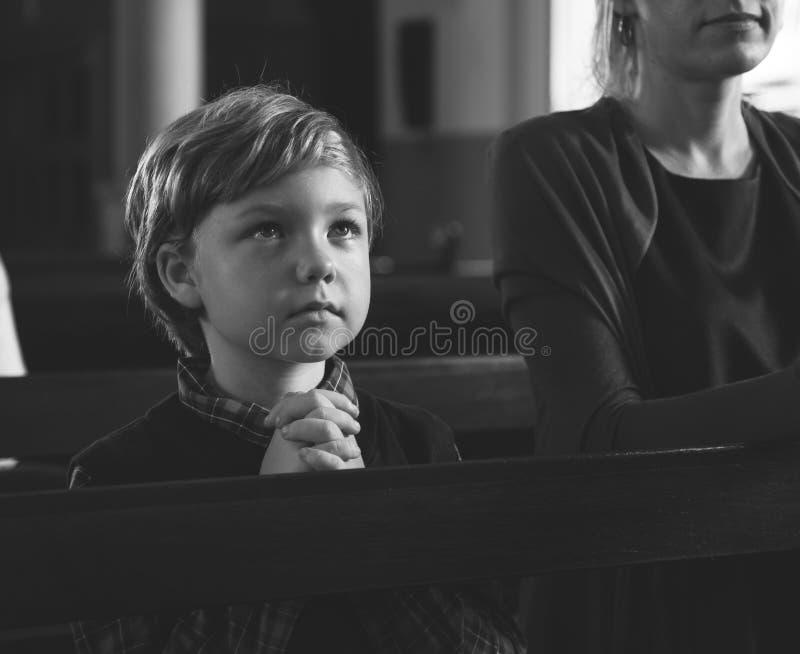 Weinig jongen die binnen een kerk bidden royalty-vrije stock foto