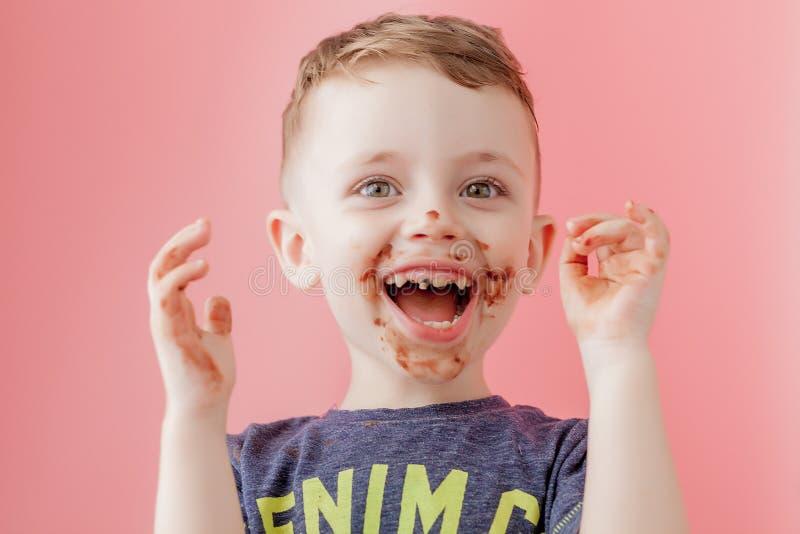 Weinig jongen die chocolade eten Leuke gelukkige die jongen met chocolade rond zijn mond wordt gesmeerd Kindconcept royalty-vrije stock afbeeldingen