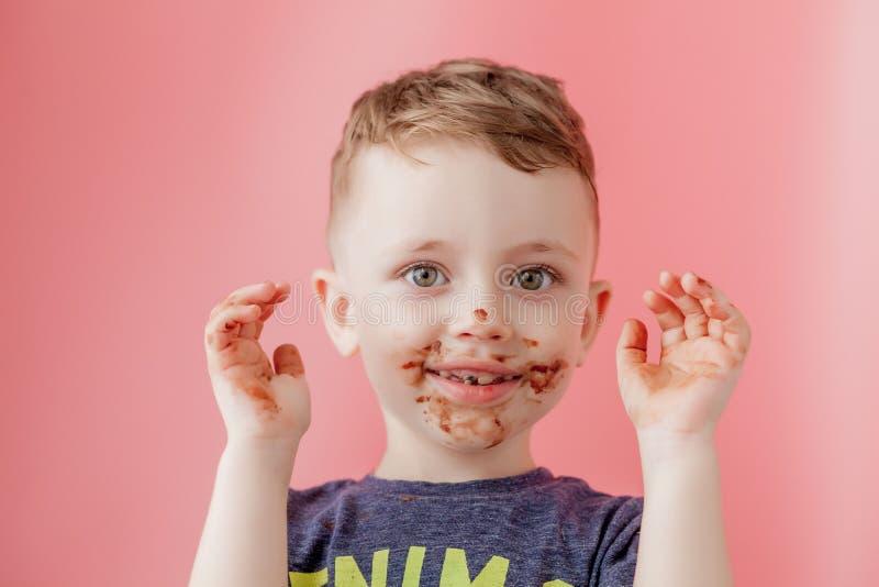 Weinig jongen die chocolade eten Leuke gelukkige die jongen met chocolade rond zijn mond wordt gesmeerd Kindconcept stock foto's