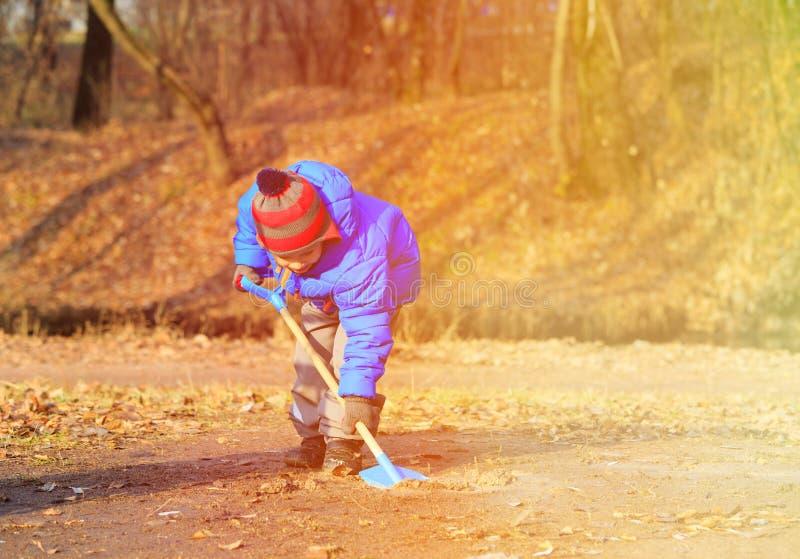 Weinig jongen die in daling, de activiteiten van de herfstjonge geitjes graven stock afbeelding
