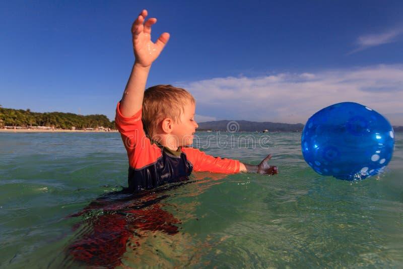 Weinig jongen die de bal in water spelen stock fotografie
