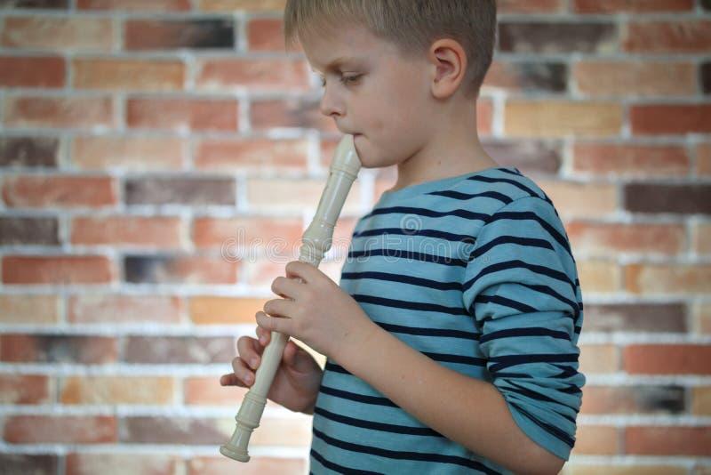 Weinig jongen die de fluit thuis spelen stock afbeeldingen