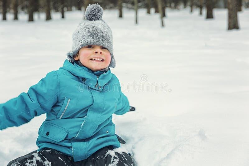 Weinig jongen die in de sneeuw en het lachen spelen royalty-vrije stock fotografie