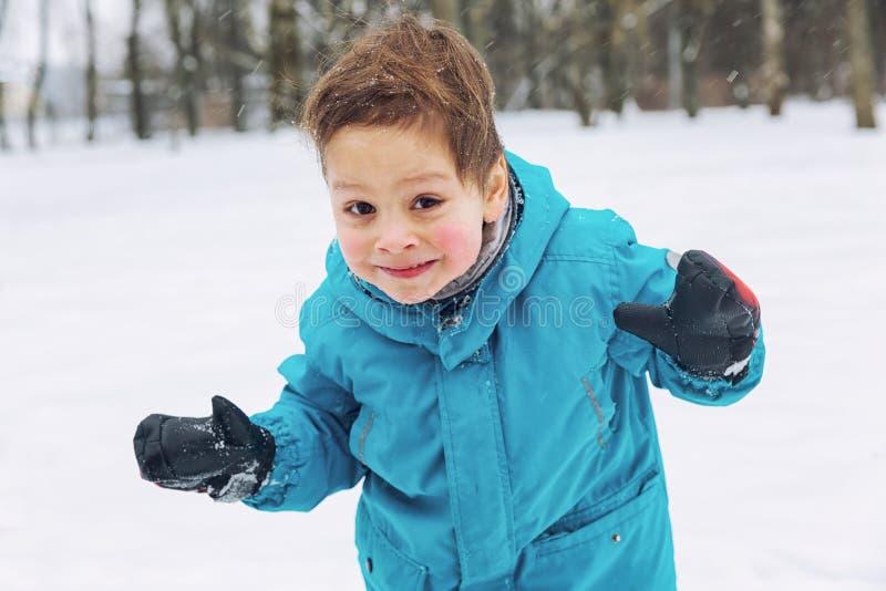 Weinig jongen die in de sneeuw en het lachen spelen royalty-vrije stock foto's
