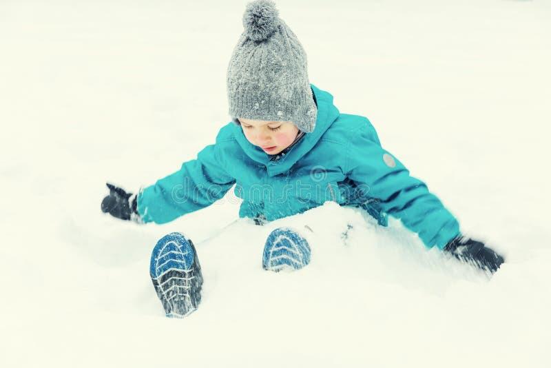 Weinig jongen die in de sneeuw en het lachen spelen stock afbeelding