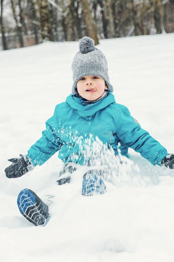 Weinig jongen die in de sneeuw en het lachen spelen stock afbeeldingen