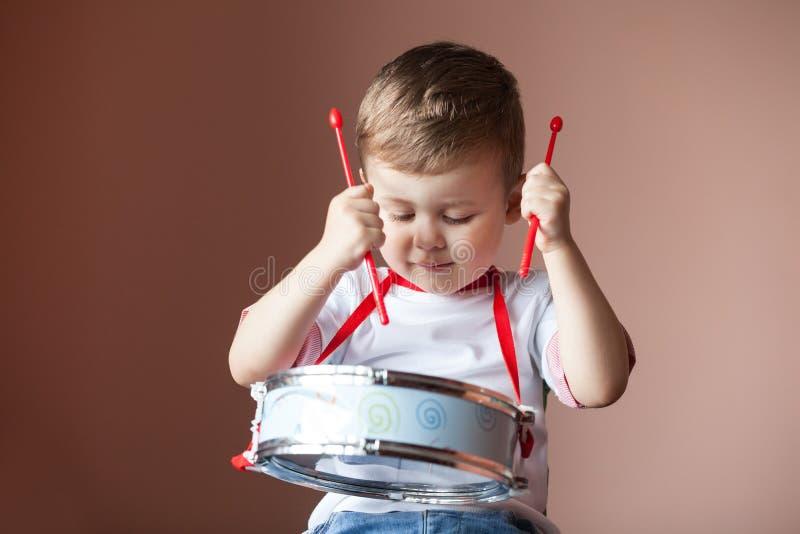 Weinig jongen die de trommel spelen het concept van de kindontwikkeling royalty-vrije stock afbeelding