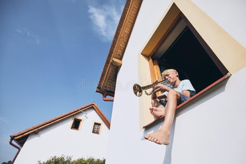 Weinig jongen die de trompet spelen stock foto's