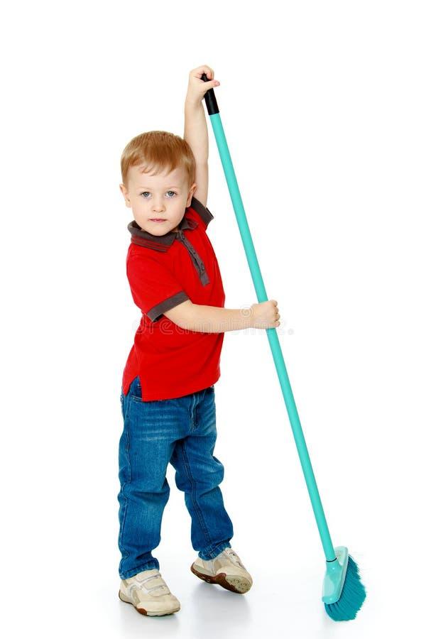 Weinig jongen die de vloerborstel vegen stock fotografie