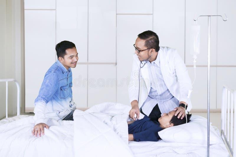 Weinig jongen die door zijn arts in het ziekenhuis onderzoeken stock fotografie