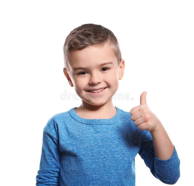 Weinig jongen die DUIM OP gebaar in gebarentaal op wit tonen stock afbeelding