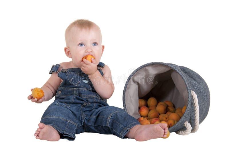 Weinig jongen die een abrikoos eten royalty-vrije stock afbeelding
