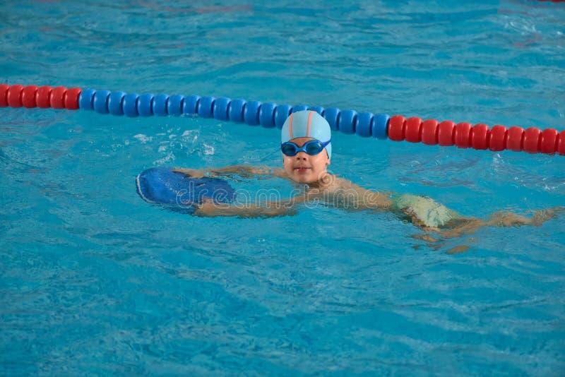 Weinig jongen die in een binnenpool leren te zwemmen stock foto