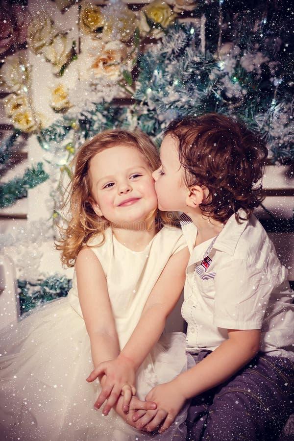 Weinig jongen die een meisje kussen stock foto