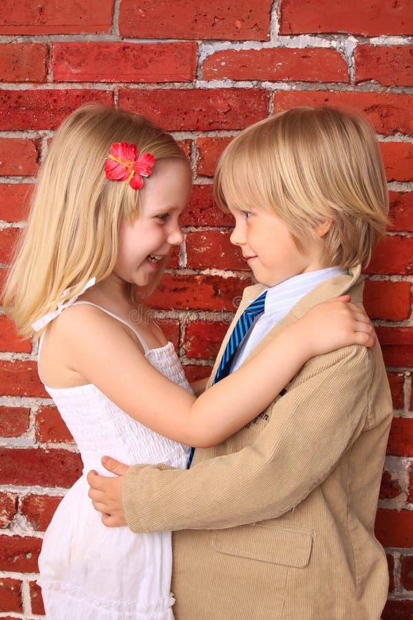 Weinig jongen die een mooi meisje koestert. Het concept van de liefde royalty-vrije stock afbeelding