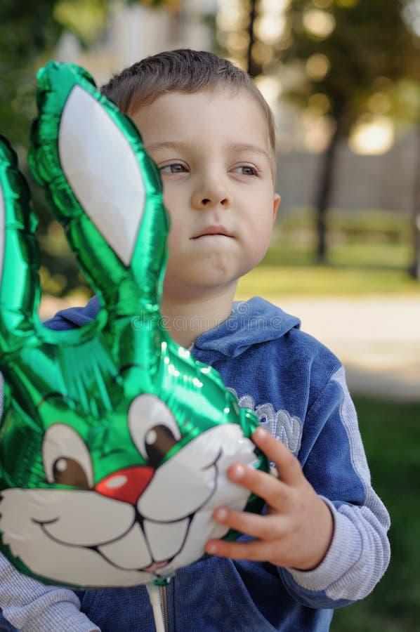 Weinig jongen die een opblaasbaar konijn houden stock afbeelding