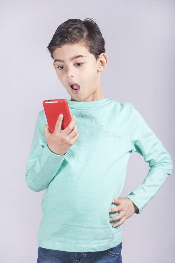 Weinig jongen die een slimme telefoon met behulp van royalty-vrije stock foto