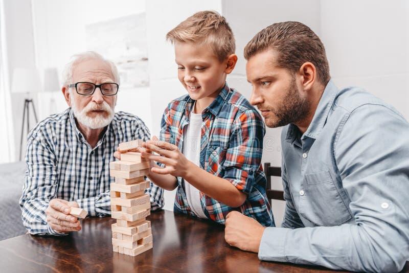 Weinig jongen die een stuk trekken uit blokken houten toren terwijl zijn vader en grootvader stock foto