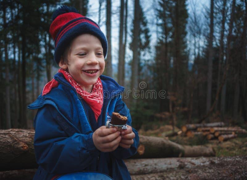 Weinig jongen die een suikergoedbar op een berg bosreis eten royalty-vrije stock fotografie