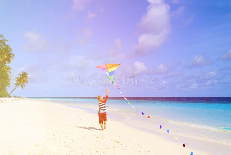 Weinig jongen die een vlieger op tropisch strand vliegen royalty-vrije stock afbeelding