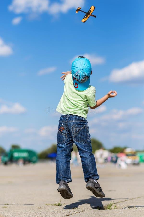 Weinig jongen die een vliegtuigmodel lanceren terwijl het springen royalty-vrije stock foto
