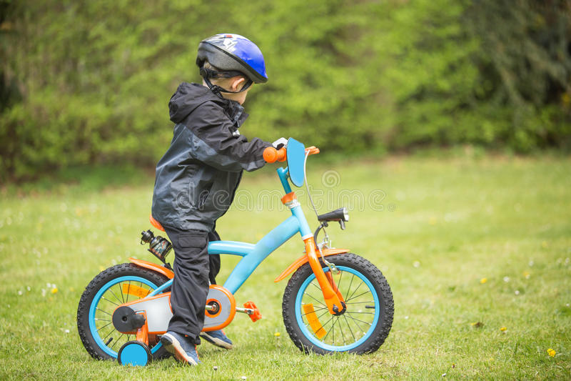 Weinig jongen die eerste fiets leren te berijden stock afbeeldingen