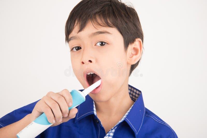 Weinig jongen die elektrische tandenborstels tandgezondheidszorg op witte achtergrond gebruiken royalty-vrije stock foto