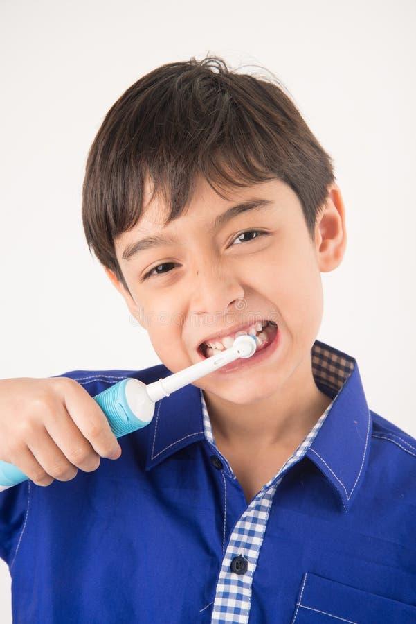 Weinig jongen die elektrische tandenborstels tandgezondheidszorg op witte achtergrond gebruiken stock fotografie