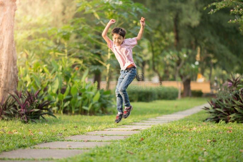 Weinig jongen die en in het park springen lopen openlucht stock fotografie