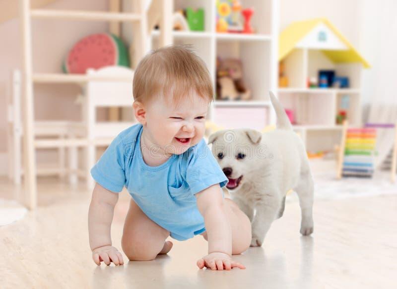 Weinig jongen die en met aanbiddelijk puppy thuis kruipen spelen stock afbeeldingen