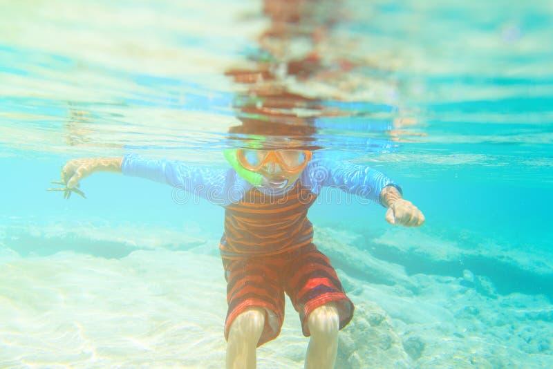Weinig jongen die en in oceaan zwemmen snorking royalty-vrije stock foto