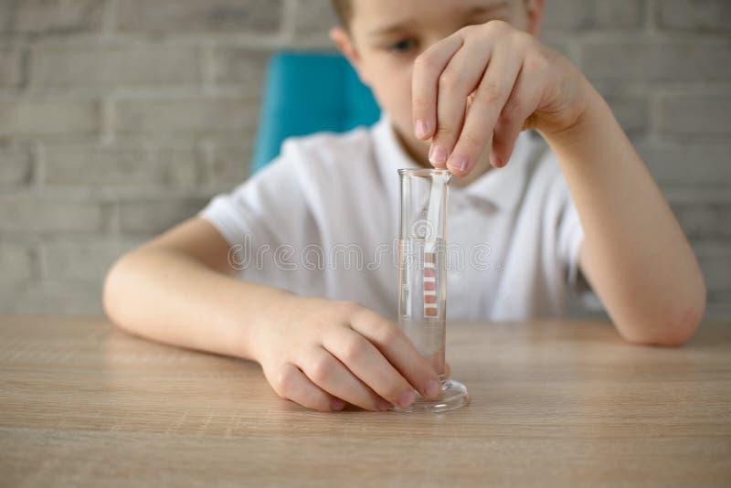 Weinig jongen die experiment op water leiden stock afbeelding