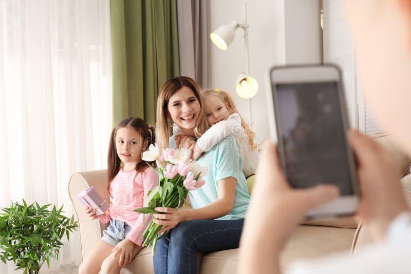 Weinig jongen die foto van zijn leuke kleine zusters en moeder thuis nemen stock foto's