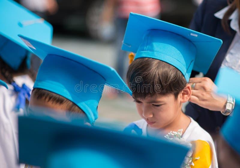 Weinig jongen die gediplomeerde hhat eenvormig op kleuterschoolschool tonen royalty-vrije stock afbeelding