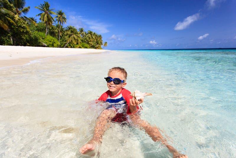 Weinig jongen die gevonden shell op strand zwemmen royalty-vrije stock foto