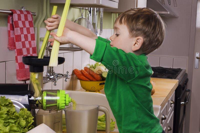 Weinig jongen die groen sap maken stock foto's