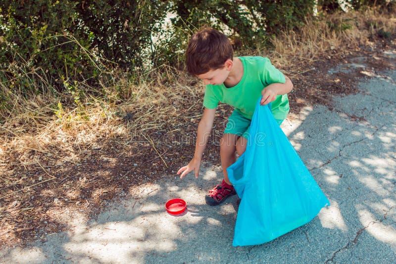 Weinig jongen die huisvuil op het park verzamelen terwijl het houden van een blauwe plastic zak royalty-vrije stock afbeeldingen