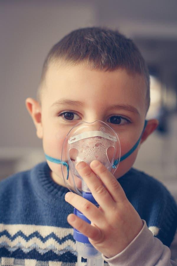 Weinig jongen die inhaleertoestel met behulp van stock afbeelding