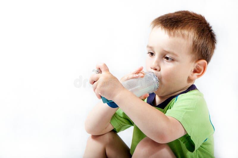 Weinig jongen die inhaleertoestel voor astma met behulp van royalty-vrije stock foto's