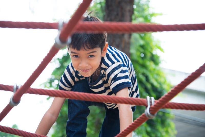 Weinig jongen die kabel beklimmen bij speelplaats stock foto's