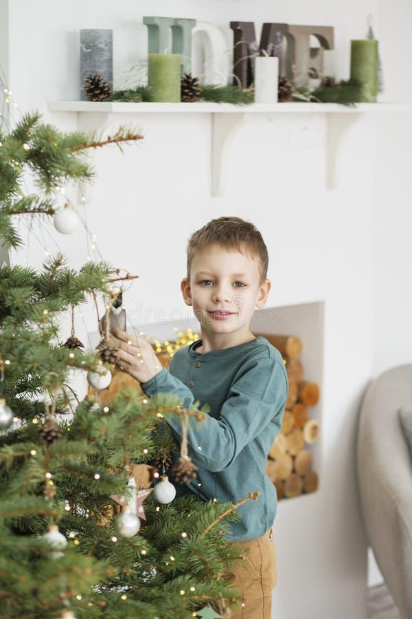 Weinig jongen die Kerstmisboom met speelgoed en ballen verfraaien Leuk jong geitje die huis voor Kerstmisviering voorbereiden Het royalty-vrije stock afbeelding