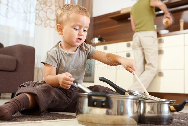 Weinig jongen die in keuken speelt stock foto's