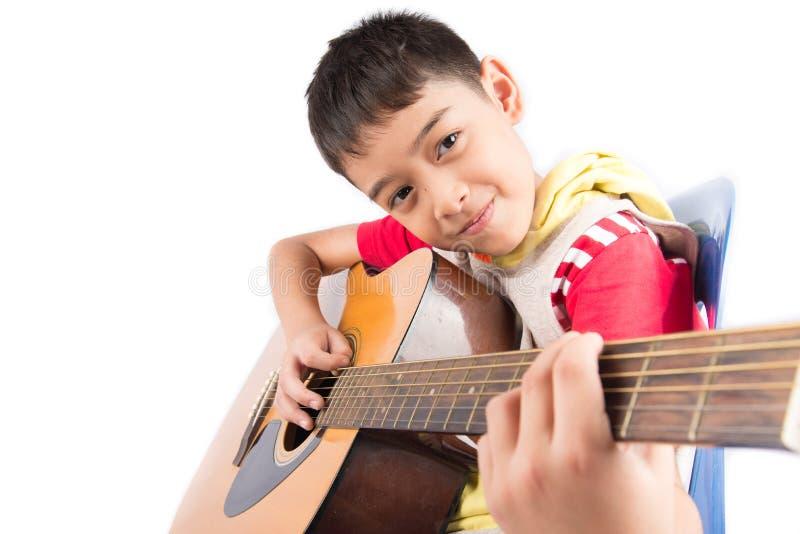Weinig jongen die klassieke gitaarcursus op witte achtergrond spelen royalty-vrije stock afbeeldingen