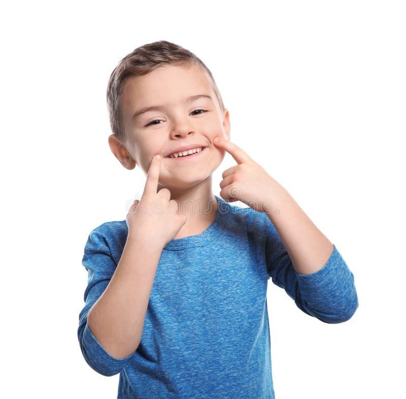 Weinig jongen die LACHgebaar in gebarentaal op wit tonen stock afbeeldingen